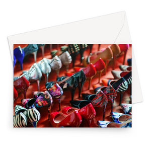 Greeting card of rows of women's high heel shoes on red floor
