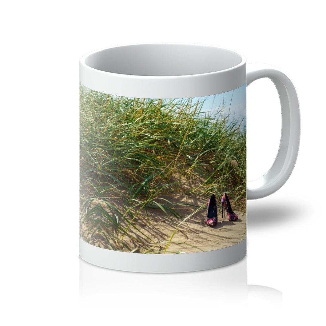 Tea or Coffee mug showing a pair of colourful ladies high heeled shoes on a grassy sand dune at the beach