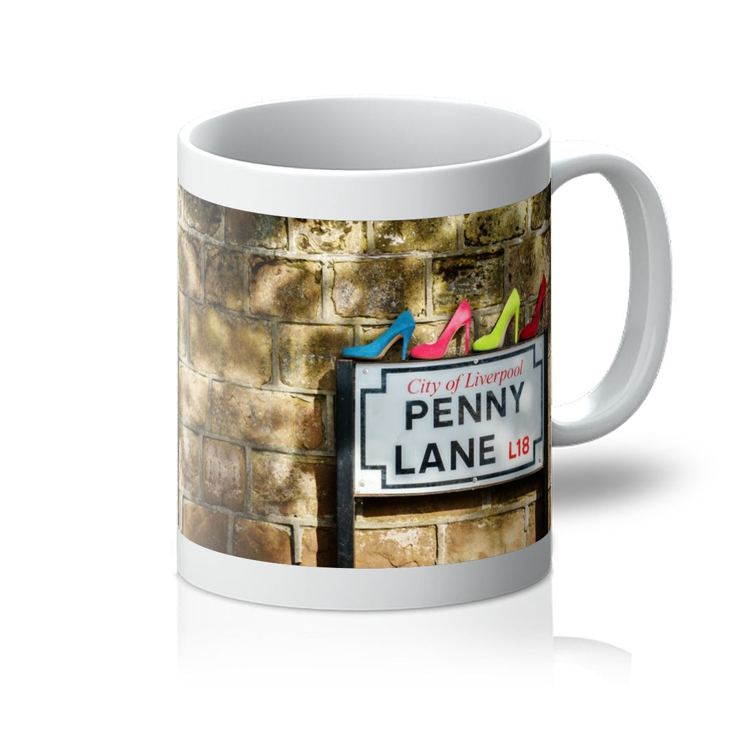 Tea or Coffee mug showing four pairs of ladies shoes, in colours of Sergeant Pepper, atop of the Penny Lane street sign in Liverpool