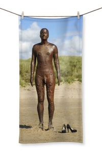 Towel showing Another Place statue by antony gormley with pair of high heal shoes on the beach