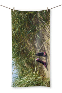Towel showing a pair of colourful ladies high heeled shoes on a grassy sand dune at the beach