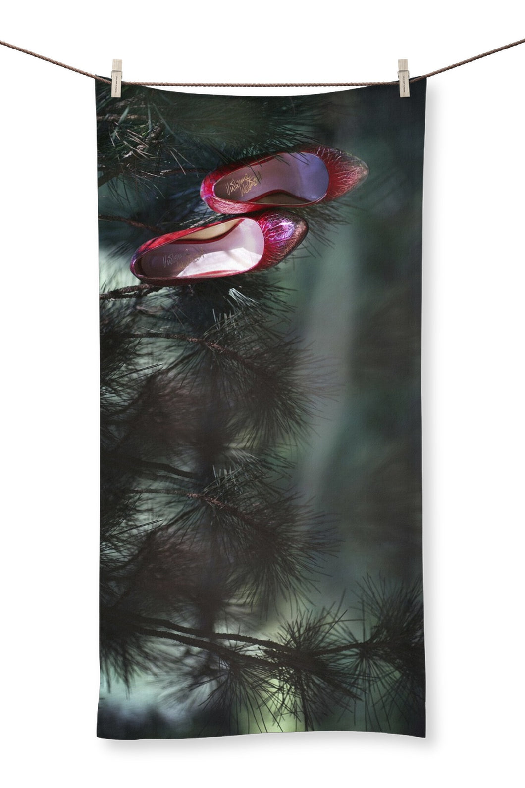 Towel showing pair of ruby coloured ladies high heeled shoes hung from branch of a green mistletoe tree