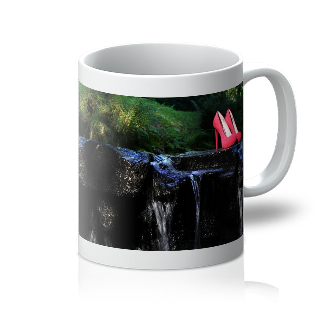 Tea or Coffee mug showing pair of red ladies high heeled shoes placed on a rock in a river