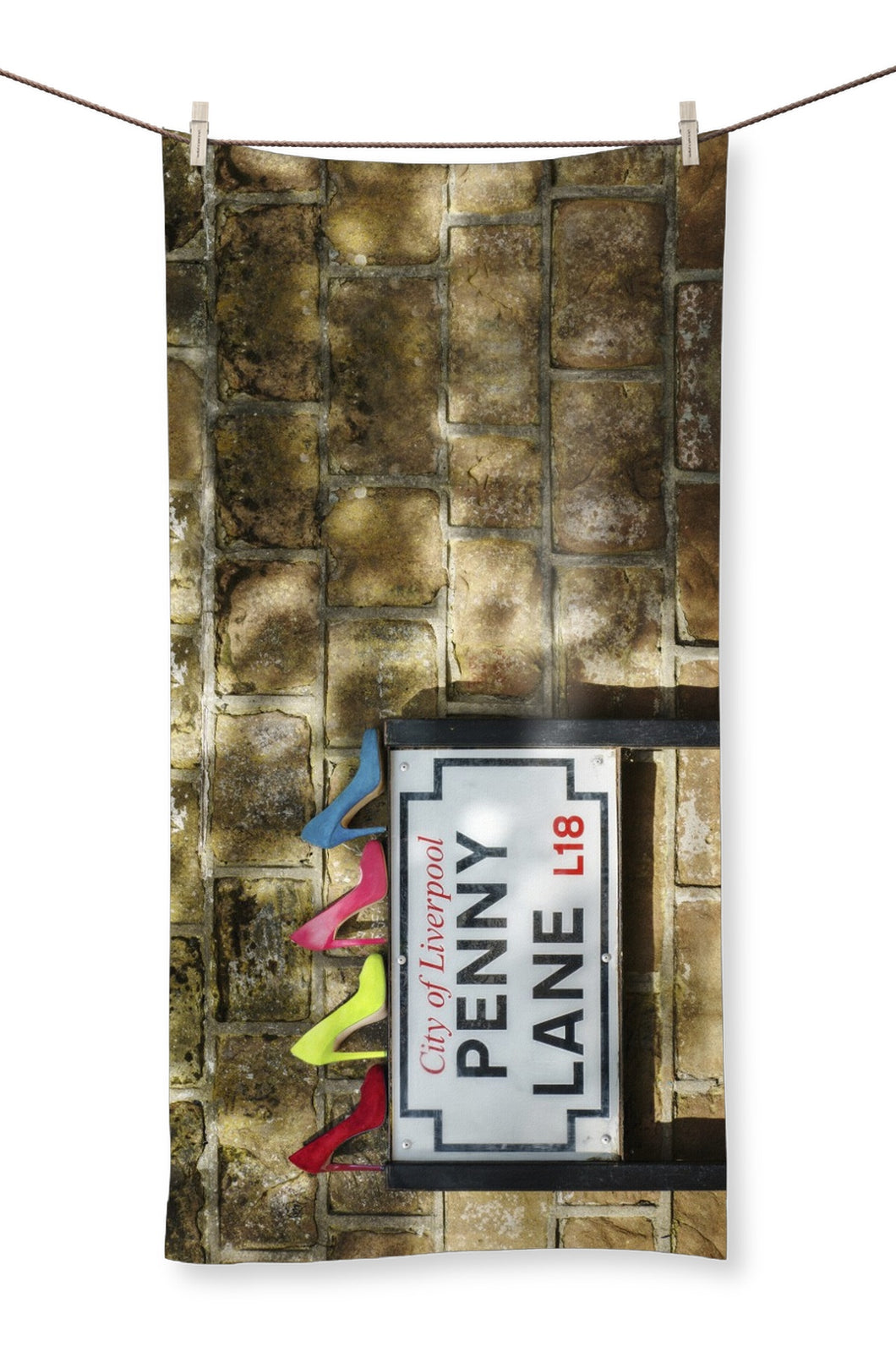 Towel showing four pairs of ladies shoes, in colours of Sergeant Pepper, atop of the Penny Lane street sign in Liverpool