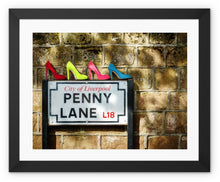 Load image into Gallery viewer, Framed print with black border of four pairs of ladies shoes, in colours of Sergeant Pepper, atop of the Penny Lane street sign in Liverpool