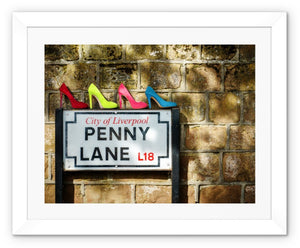 Framed print with white border of four pairs of ladies shoes, in colours of Sergeant Pepper, atop of the Penny Lane street sign in Liverpool