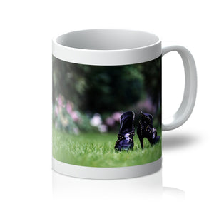 Tea or Coffee Mug showing close up of pair of purple high heeled ladies ankle boots, on their own in a garden