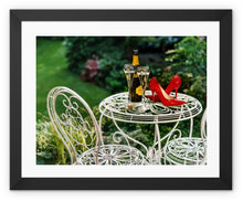 Load image into Gallery viewer, Framed print with black border showing red high heeled shoes sitting on a garden table adjacent to a bottle of champagne, along with two filled champagne glass flutes