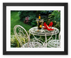 Framed print with black border showing red high heeled shoes sitting on a garden table adjacent to a bottle of champagne, along with two filled champagne glass flutes