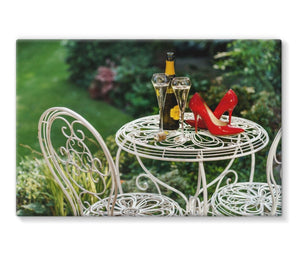 Canvas print of red high heeled shoes sitting on a garden table adjacent to a bottle of champagne, along with two filled champagne glass flutes