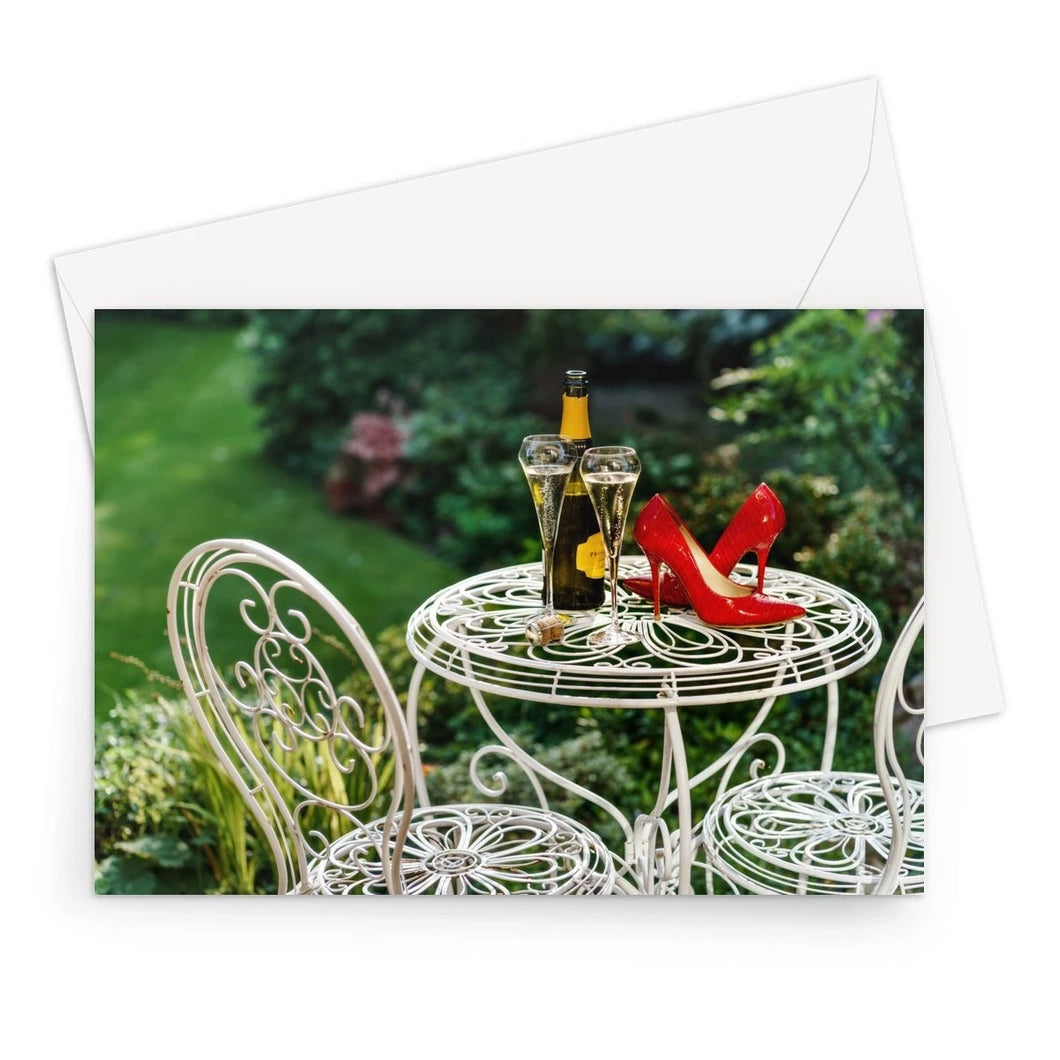 Greeting card of red high heeled shoes sitting on a garden table adjacent to a bottle of champagne, along with two filled champagne glass flutes