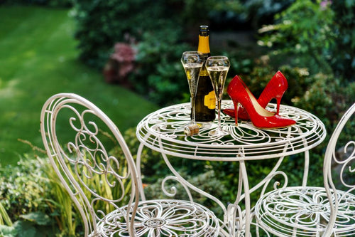 red high heeled shoes sitting on a garden table adjacent to a bottle of champagne, along with two filled champagne glass flutes