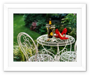 Framed print with white border showing red high heeled shoes sitting on a garden table adjacent to a bottle of champagne, along with two filled champagne glass flutes
