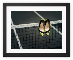 Framed print  with black border showing Pair of women's high heeled shoes hanging over the top of a tennis net