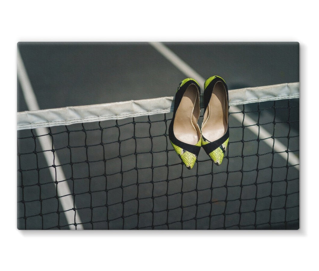Canvas print of Pair of women's high heeled shoes hanging over the top of a tennis net