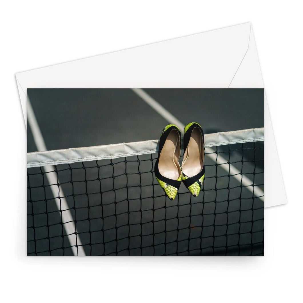 Greeting card showing Pair of women's high heeled shoes hanging over the top of a tennis net