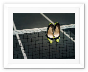 Framed print with white border showing Pair of women's high heeled shoes hanging over the top of a tennis net