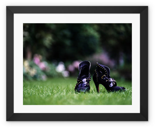 Framed print with black border showing close up of pair of purple high heeled ladies ankle boots, on their own in a garden