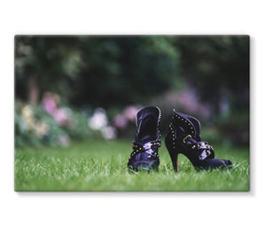 Canvas print showing close up of pair of purple high heeled ladies ankle boots, on their own in a garden