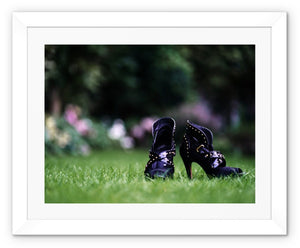 Framed print with white border showing close up of pair of purple high heeled ladies ankle boots, on their own in a garden