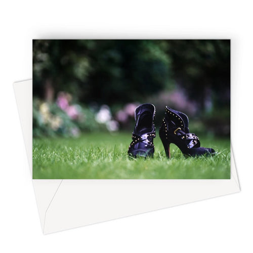 Greeting card showing close up of pair of purple high heeled ladies ankle boots, on their own in a garden