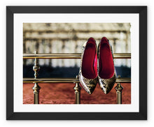 Load image into Gallery viewer, Framed Print with black border pair of ladies high heeled shoes, with  red interior and snake skin pattern, hanging off bed frame
