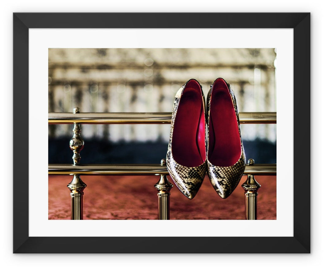 Framed Print with black border pair of ladies high heeled shoes, with  red interior and snake skin pattern, hanging off bed frame