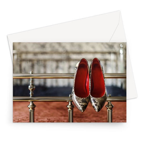 Greeting card showing pair of ladies high heeled shoes, with  red interior and snake skin pattern, hanging off bed frame