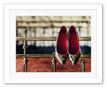 Load image into Gallery viewer, Framed Print with white border pair of ladies high heeled shoes, with  red interior and snake skin pattern, hanging off bed frame