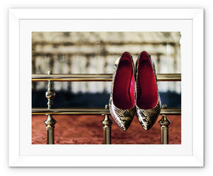 Framed Print with white border pair of ladies high heeled shoes, with  red interior and snake skin pattern, hanging off bed frame