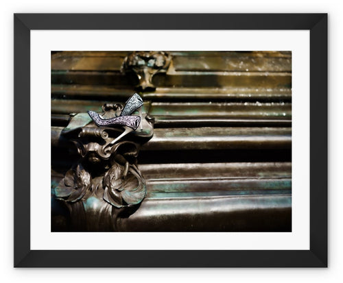 Framed print with black border of womens shoes abandoned at a fountain