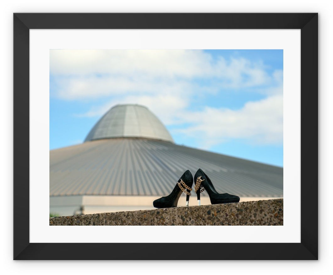 Framed print with black border showing a pair of black high heeled ladies shoes in front of a building, shaped like a UFO spaceshipa