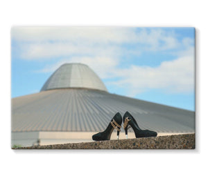 canvas print showing a pair of black high heeled ladies shoes in front of a building, shaped like a UFO spaceshipa