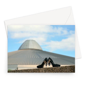 Greeting card showing a pair of black high heeled ladies shoes in front of a building, shaped like a UFO spaceshipa
