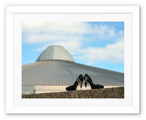 Framed print with white border showing a pair of black high heeled ladies shoes in front of a building, shaped like a UFO spaceshipa