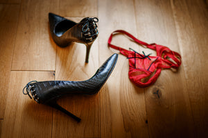 pair of red knickers abandoned on wooden floor next to pair of black high heeled ladies shoes