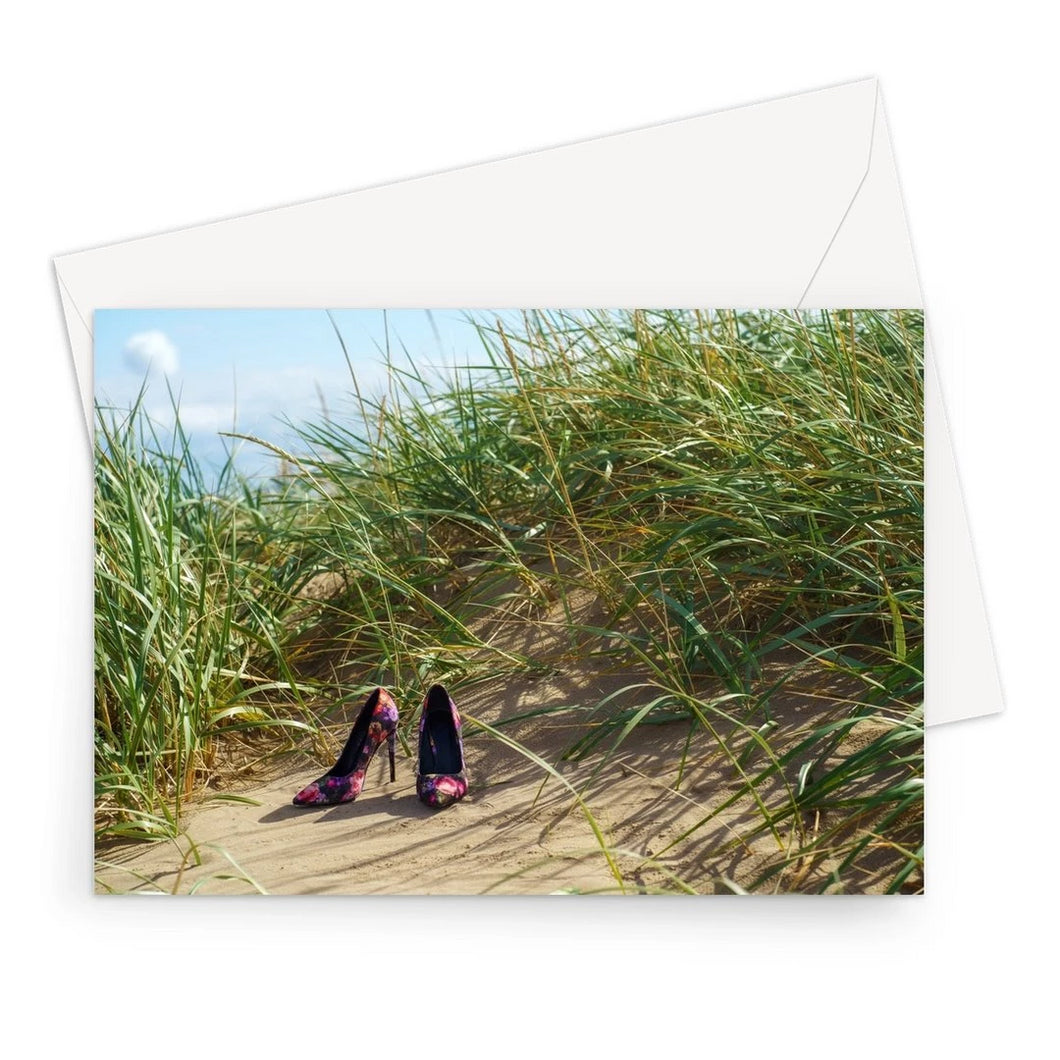 Greeting card showing a pair of colourful ladies high heeled shoes on a grassy sand dune at the beach