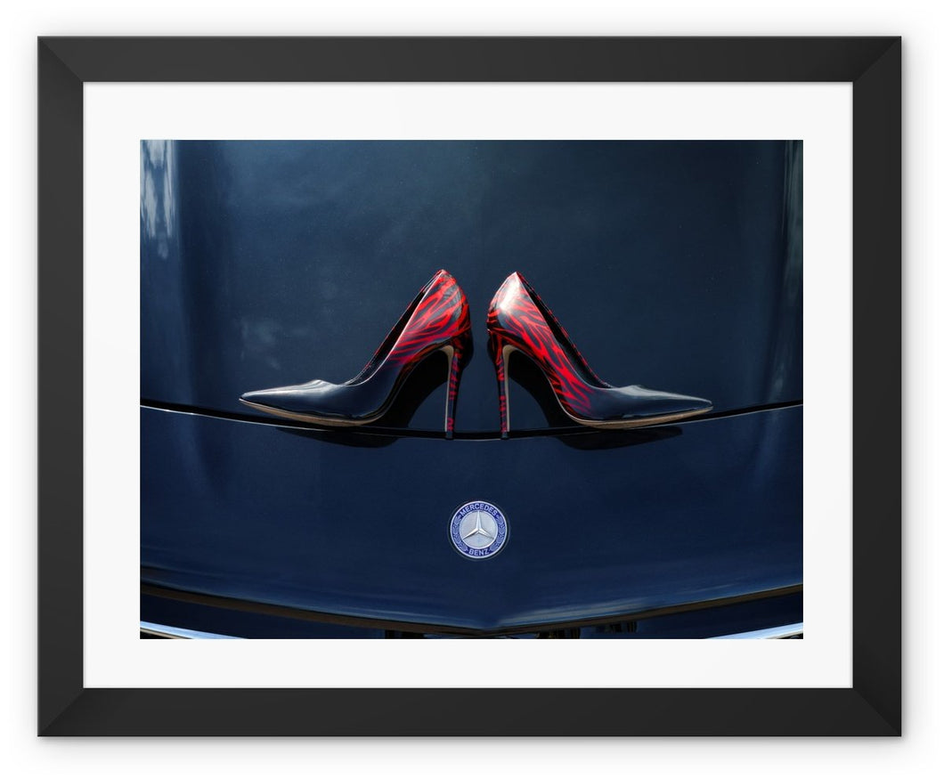 Framed print with black border showing a pair of Ladies high heeled red and black shoes on bonnet of a black Mercedes-Benz car