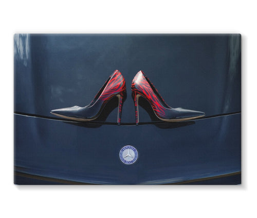 Canvas print with black border showing a pair of Ladies high heeled red and black shoes on bonnet of a black Mercedes-Benz car