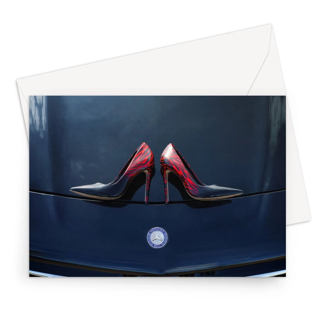 Greeting card showing a pair of Ladies high heeled red and black shoes on bonnet of a black Mercedes-Benz car