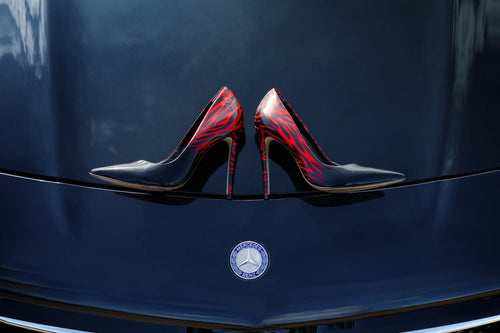 a pair of Ladies high heeled red and black shoes on bonnet of a black Mercedes-Benz car