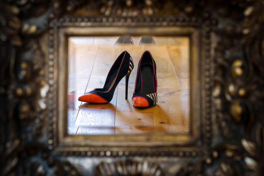 reflection in a mirror of pair of orange tipped black ladies high heeled shoes