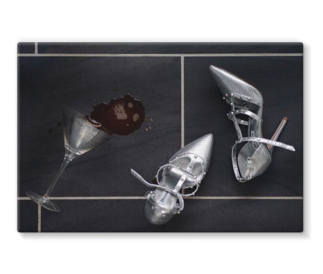Canvas Print with black border showing spilt espresso martini cocktail over titled floor, next to pair of silver high heeled ladies shoes