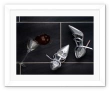 Load image into Gallery viewer, Framed Print with white border showing spilt espresso martini cocktail over titled floor, next to pair of silver high heeled ladies shoes