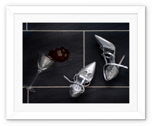 Framed Print with white border showing spilt espresso martini cocktail over titled floor, next to pair of silver high heeled ladies shoes