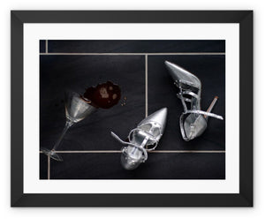 Framed Print with black border showing spilt espresso martini cocktail over titled floor, next to pair of silver high heeled ladies shoes