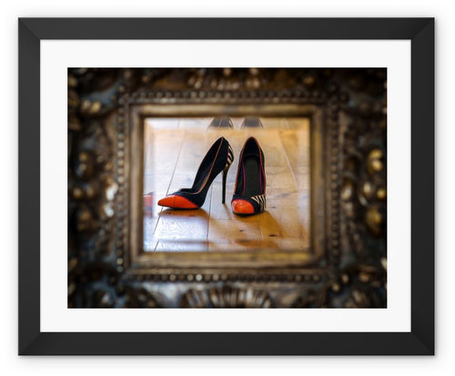Framed print with black border of reflection in a mirror of pair of orange tipped black ladies high heeled shoes