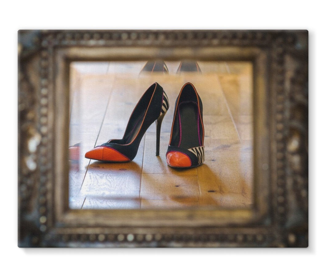 Canvas print of reflection in a mirror of pair of orange tipped black ladies high heeled shoes