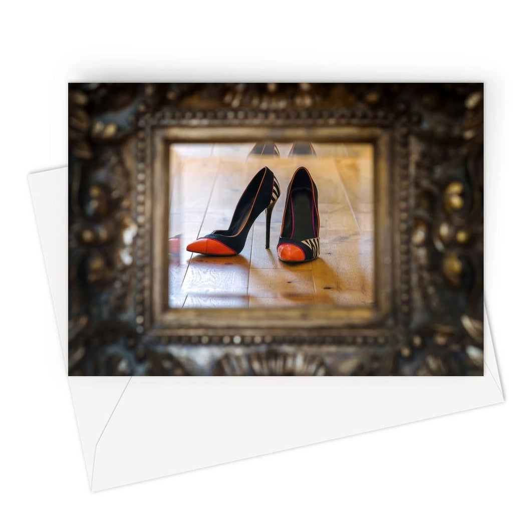 Greeting card of reflection in a mirror of pair of orange tipped black ladies high heeled shoes