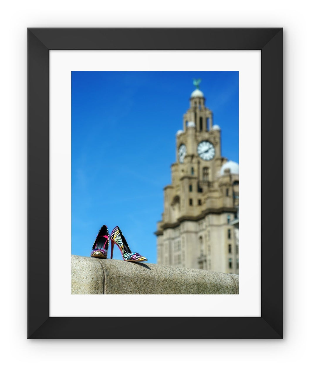 Framed print with black border showing Liverpool liver building with pair of multi-coloured high heeled shoes in foreground